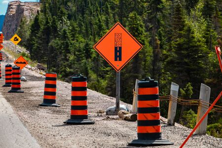 Paved surface ends ahead orange sign, Temporary condition road signs barrels, warning symbols, on the right roadside, under construction asphalt road