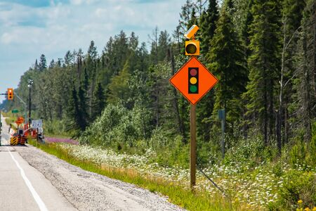 Temporary condition road warning signs on the roadside before road work zone, signal traffic lights ahead. Slow down. with lamps, Canadian rural roads Reklamní fotografie