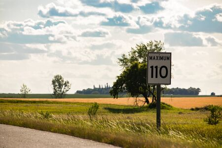 110 km maximum speed limit sign on the roadside against yellow prairies and plains view on the Canadian rural country roads