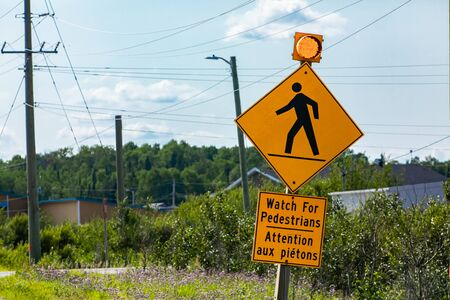 Warning for pedestrians, Warning road sign, Watch for pedestrians bilingual sign French and English, with yellow lamp, Canadian rural area background Reklamní fotografie