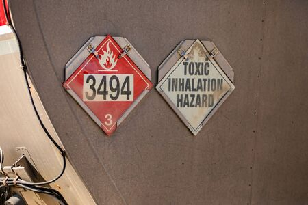 Close up on red Fire sign with 3494 fire symbol and white toxic inhalation hazard sign, warning signs on metal tank truck back