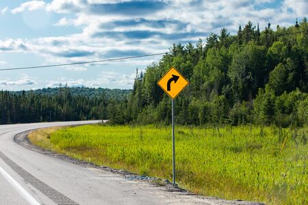 Slight bend or curve in the road ahead, Warning for a curve to the right, Warning Road Sign on the roadside with pine trees forest background Reklamní fotografie