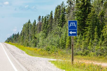 Rest area blue sign with an arrow to left symbol, pine trees forest on the roadsides, Canadian rural roads during a sunny day