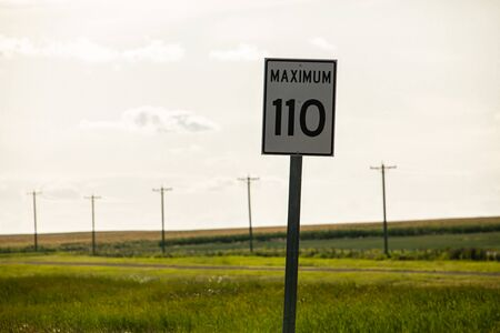 Selective focus view of 110 maximum speed limit sign on the roadside, against prairies and plains views on the Canadian rural country roads Reklamní fotografie