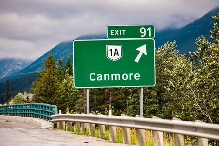 Information road green sign, the next exit after 91 km, Canmore, 1A road symbol, Canadian rural roadside forests in the background, Alberta, Canada