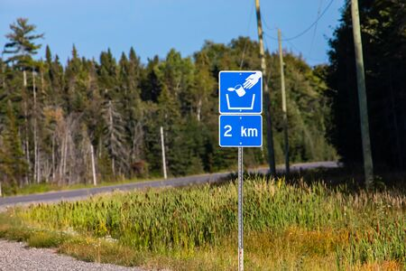Trash symbol on a blue road sign after 2 km, pine trees forest on the roadsides, Canadian rural roads during a sunny day
