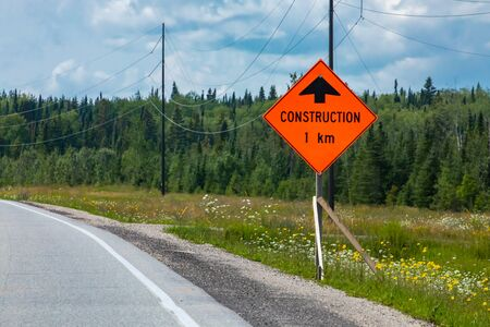 Temporary condition road signs, Construction work one kilometre ahead. on Canadian rural country roadside pine trees background, warning orange symbol
