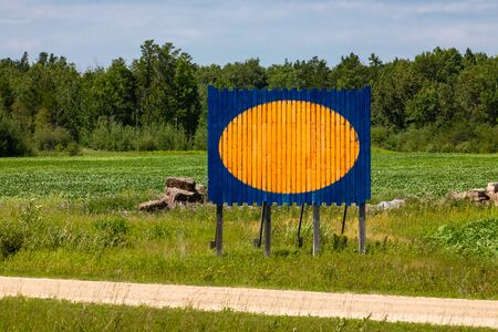 Blue wooden empty billboard with orange yellow circle, big round copy space, in a pasture with forest trees in the background