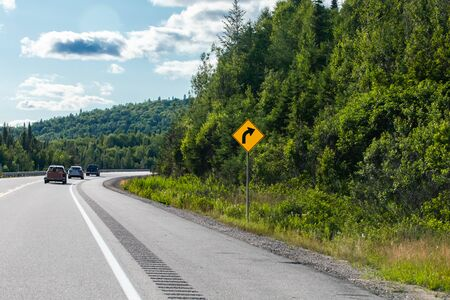 Vehicles on the road curve with warning slight bend or curve in the road ahead to the right sign, a Canadian rural road between forests