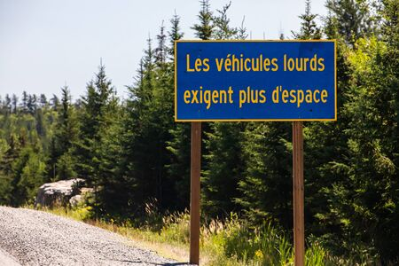 Blue Information Road Sign with french yellow writing, heavy vehicles require more space. on rural country roadside, trees background, Ontario, Canada