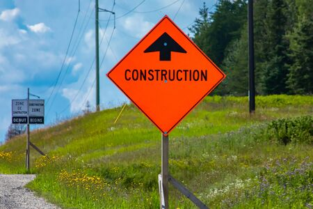 Temporary condition road signs, Construction work. on Canadian rural country roadside with pine trees background, close up warning orange symbol