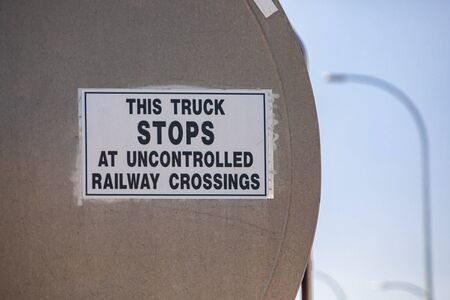 a selective focus on Warning and Information white a poster sign says This truck STOPS at uncontrolled railway crossing, on metal tank truck back Reklamní fotografie