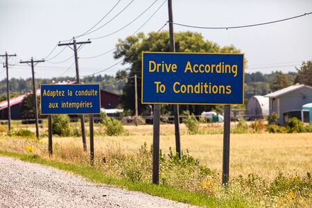 French, English Information road Signs, Drive According To Conditions. On Canadian rural country roadside with farms in the background, Ontario Canada