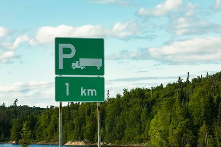 Trucks Parking Green Sign with a white long truck symbol, after 1 km, with lake, pine trees, and cloudy sky in the background