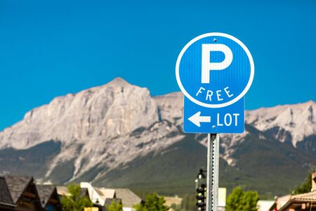 selective focus on free Parking Lot blue sign with an arrow left, against mountains and the blue sky, British Columbia, Canada