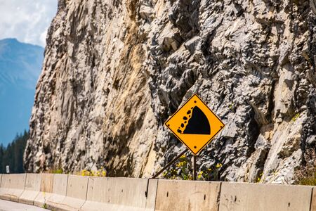 Watch for fallen rock and be prepared to avoid a collision sign. Warning road signs on cement barriers, with rocky slope background Reklamní fotografie