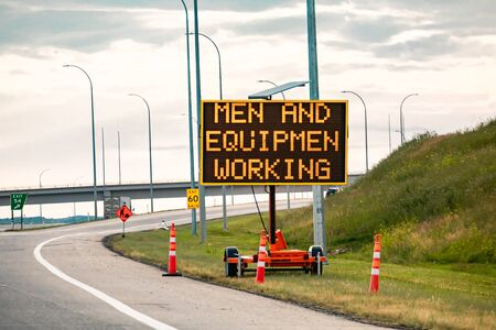 Temporary condition Variable message sign with orange barrels on the right roadside Men and equipment working, work zone on the Canadian highway roads Reklamní fotografie