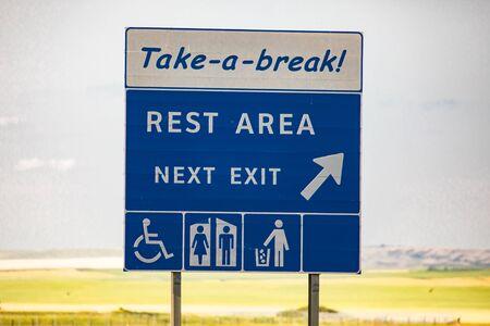 Pause machen, Rastplatz in der nächsten Ausfahrt, Aufgeräumter Mann, Toiletten, Symbole für besondere Bedürfnisse., Informationsstraße blaues Schild gegen gelbe Prärien und Ebenen Standard-Bild