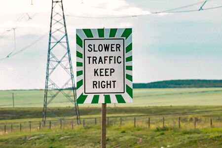 Slow traffic on multi-lane roads must keep right. Regulatory road sign with white and green lines frame. transmission tower in the background