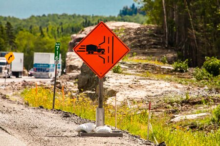 Truck entrance on the left side of the road ahead, Temporary condition road signs, warning symbols on the right roadside Reklamní fotografie