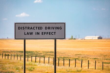 Information Road white Sign, Distracted driving law in effect., on Canadian rural country roadside, against farms and prairies, plains
