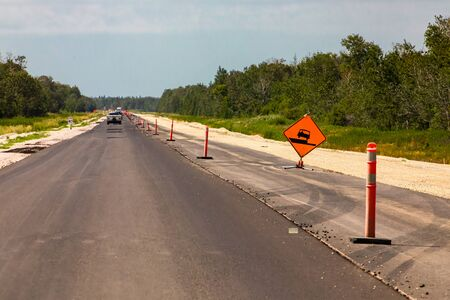 road under construction with new asphalt, Temporary condition signs, and Orange barrels on the right roadside, Canadian rural country roads