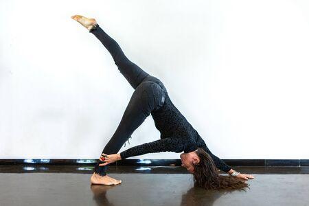 A healthy woman is seen in Eka Pada Adho Mukha Svanasana, one legged downward facing dog pose, during a Vinyasa yoga workout, against a white wall