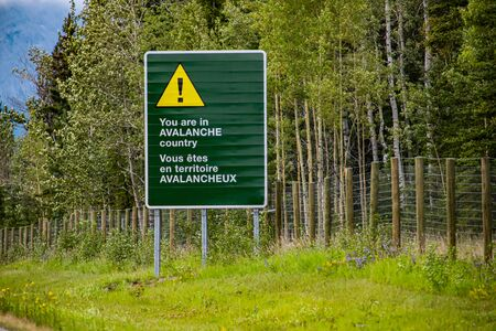 two languages French and English Information road Bilingual green sign on roadside, you are in avalanche country with Yellow warning triangle symbol Standard-Bild