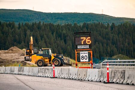 Radar Speed Sign displays vehicle speed on variable sign, your speed is 76, 80km maximum limitation, road work zone Machines Excavators on background