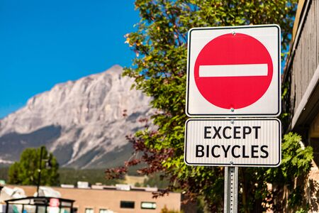 selective focus on do not enter road sign with except bicycles sign, against buildings and mountains and the blue sky, British Columbia, Canada