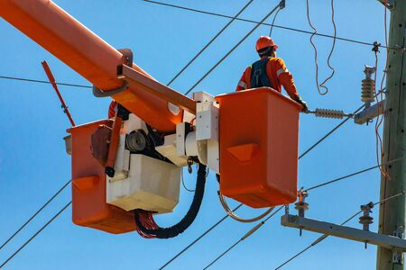 A man wearing high visibilty personal protective equipment, PPE, is seen working on high voltage overhead power cables and a utility pole at height