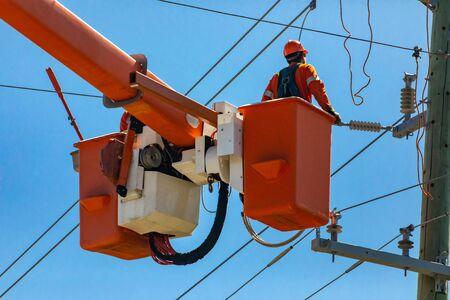 Un hombre vestido con equipo de protección personal de alta visibilidad, PPE, se ve trabajando en cables eléctricos aéreos de alta tensión y un poste de servicios públicos en altura Foto de archivo