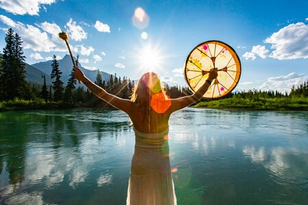 A backlit and rear view of a spiritual woman holding a powwow drum during a mindful ritual in nature, bright sun gives atmospheric mystical lens flare