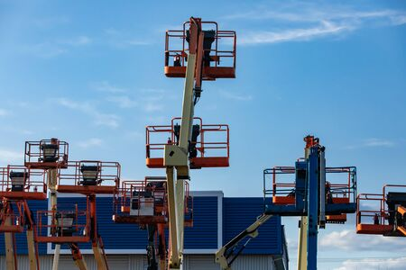 A construction industry storage unit and yard is seen with a group of mobile elevating work platforms, MEWP or cherry pickers, at rest and stored