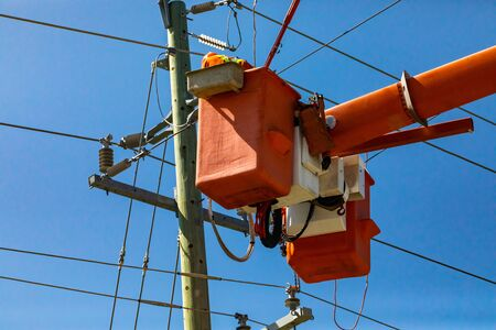 A low angle shot of a man at work in bright orange aerial work platform, cherry picker, servicing an aging wooden electricity pylon, with copy space