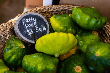 A close up view of a wicker basket filled with patty pans, a variety of summer squash, and price sign on a market stall during an agricultural fair