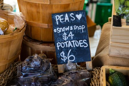 A closeup view of a traditional price sign advertising organic snow and snap peas and potatoes on a market stand during a local agricultural fair
