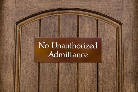 No Unauthorized Admittance, brown sign on a wooden door, sign to indicate that entry into the area where the sign is displayed is forbidden