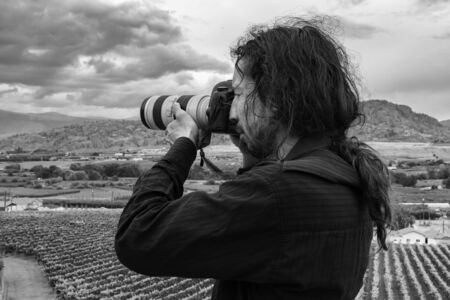 Young caucasian man photographer with long hair, back close up view taking hill high DSLR camera pictures, vineyards farms background, black and white