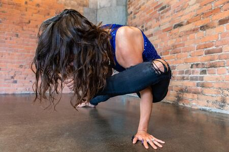 A close up and side view of a strong brunette woman balancing on her hands in an advanced posture during a Vinyasa flow yoga