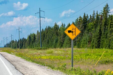 Truck entrance on the left side of the road ahead, a Warning sign on the roadside with transmission towers and pine trees forest background Stock Photo