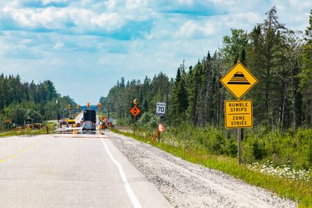 Temporary condition road warning signs on the roadside before road work zone, rumble strips on a bilingual yellow sign, Canadian rural roads Reklamní fotografie