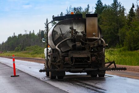 An industrial construction vehicle is seen covered in dirt and muck from the back, at work on the roadside during construction and upgrade of highway