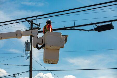 La salud y la seguridad en la industria de la construcción y el mantenimiento como obrero se ve desde abajo en un recolector de cerezas por un poste de servicios públicos