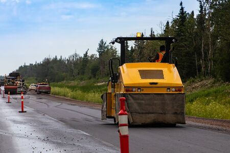 A heavy duty road roller is seen compacting asphalt subsurface during roadworks on a major freeway, transport infrastructure upgrade with copy space
