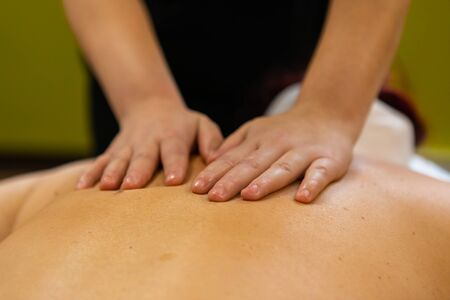 A close up view on the hands of a masseuse gently sliding hands over the back and shoulders of a stressed woman, kneading knots and muscle tension