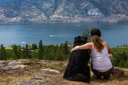pretty girl over the rocks sits and contemplates the horizon with her beloved dog with a view of the lake of the okanagan valley
