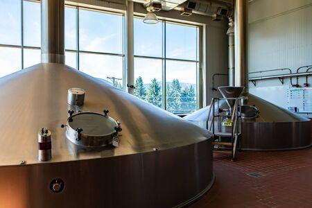 Maischeläuterbottich, zwei große Edelstahlgefäße, Brautankdeckel mit Glastür, modernes Sudhaus, Brauereiraum in großen Bierfabrikmaschinen