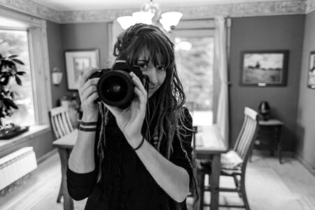 Black and white close up portrait of professional photographer hand-holding a DSLR camera. Natural beautiful girl with dreadlocks and tattoos.
