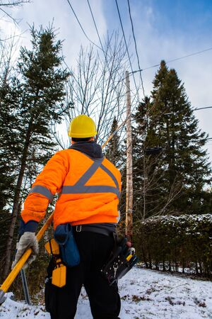 An optical fiber engineer is seen from the back, working under a telegraph pole outdoors in winter, wearing a high visibility jacket and safety helmet